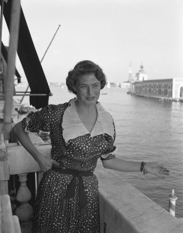 Bergman, wearing a polka-dotted dress, portrayed while posing on a terrace with the Canal Grande in the background, in Venice