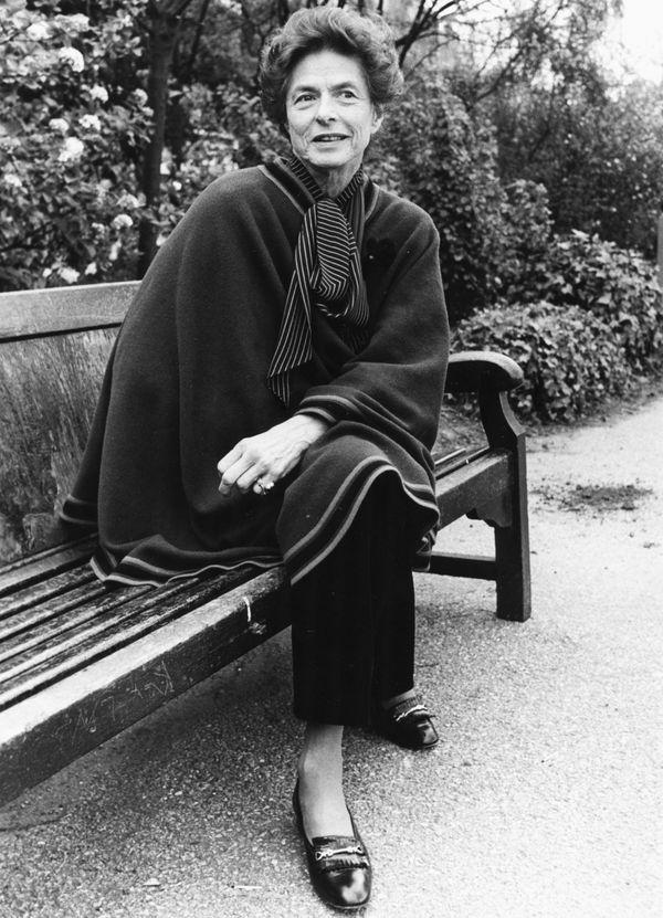 Portrait of actress Ingrid Bergman sitting on a park bench in London.