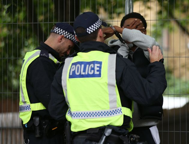 Police officers handcuff a man at Notting Hill Carnival in west