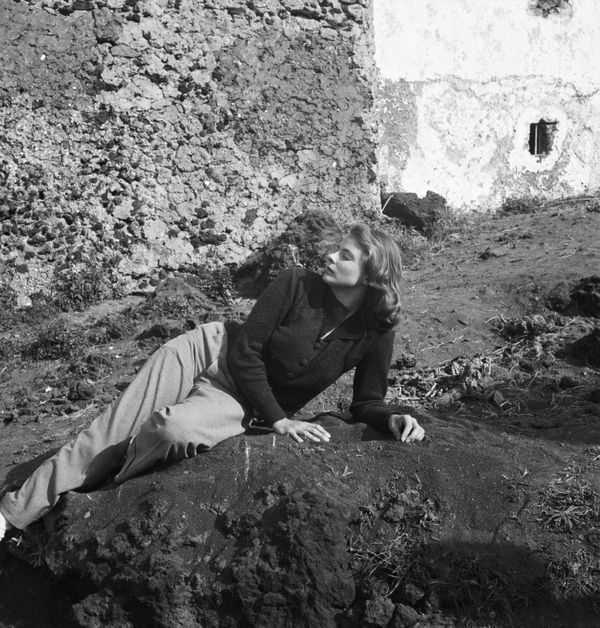 The actress lying on a hillside in the sun.