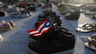 A Puerto Rican flag is seen on a pair of shoes as hundreds of pairs of shoes displayed at the Capitol to pay tribute to Hurricane Maria's victims after a research team led by Harvard University estimated that 4,645 people lost their lives, a number not confirmed by the government, in San Juan, Puerto Rico June 1, 2018. REUTERS/Alvin Baez