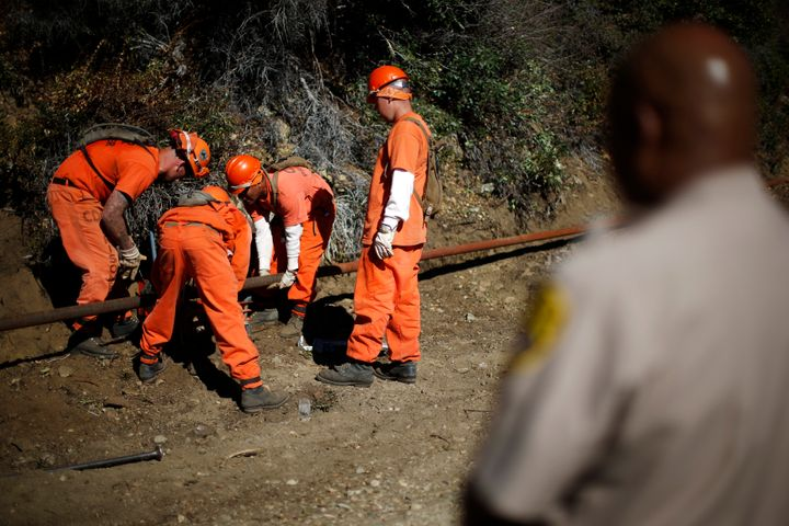 Prison inmates lay water pipe on a work project outside Oak Glen Conservation Fire Camp #35 in Yucaipa, California, on Nov. 6