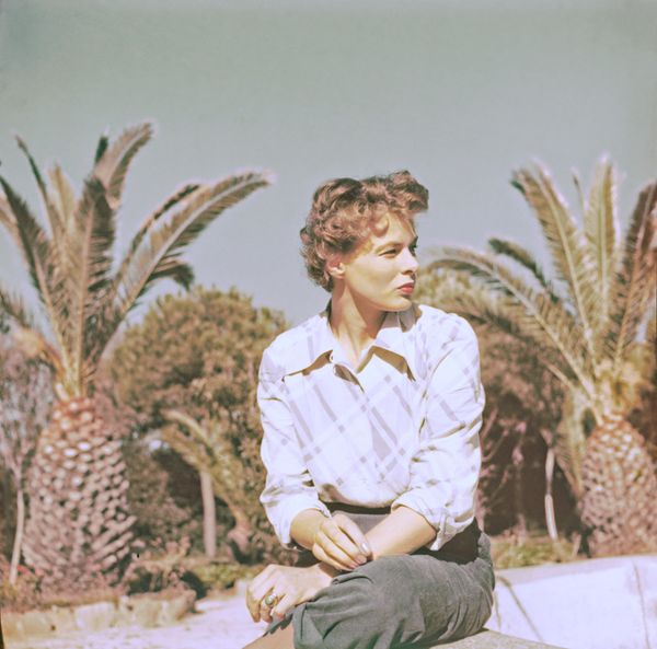 The Swedish actress sitting outside among the palm trees.