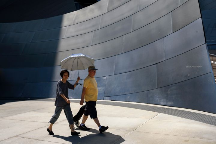 Pedestrians outside the Walt Disney Concert Hall in Los Angeles on Aug. 7 shield themselves from the sun as the temperat