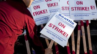 A teacher grabs a sign before walking the picket line as teachers strike outside Roosevelt High School in Seattle, Washington September 9, 2015. Classes were cancelled for 53,000 students as Seattle teachers and support staff marched in picket lines on Wednesday on what was supposed to be the first day of school, waging their first such strike in three decades after contract talks between the school district and the teachers' union failed.  REUTERS/Matt Mills McKnight