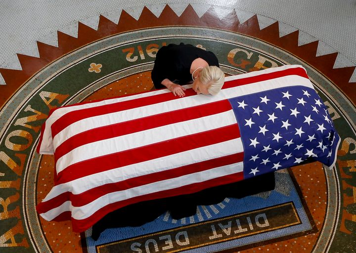 Cindy McCain kisses the casket of her husband, Sen. John McCain, during a memorial service in Phoenix at the state Capitol, A