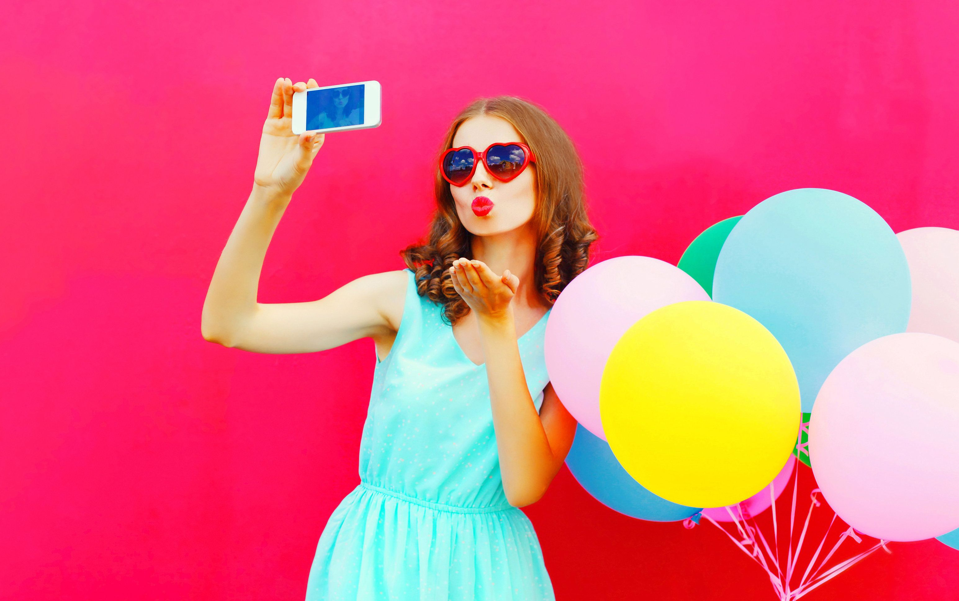 Fashion pretty woman taking a picture on a smartphone sends an air kiss over an air colorful balloons a pink background