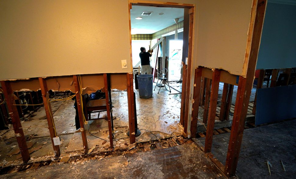 A man tears out flood damage from a home in southwestern Houston on September 2, 2017.