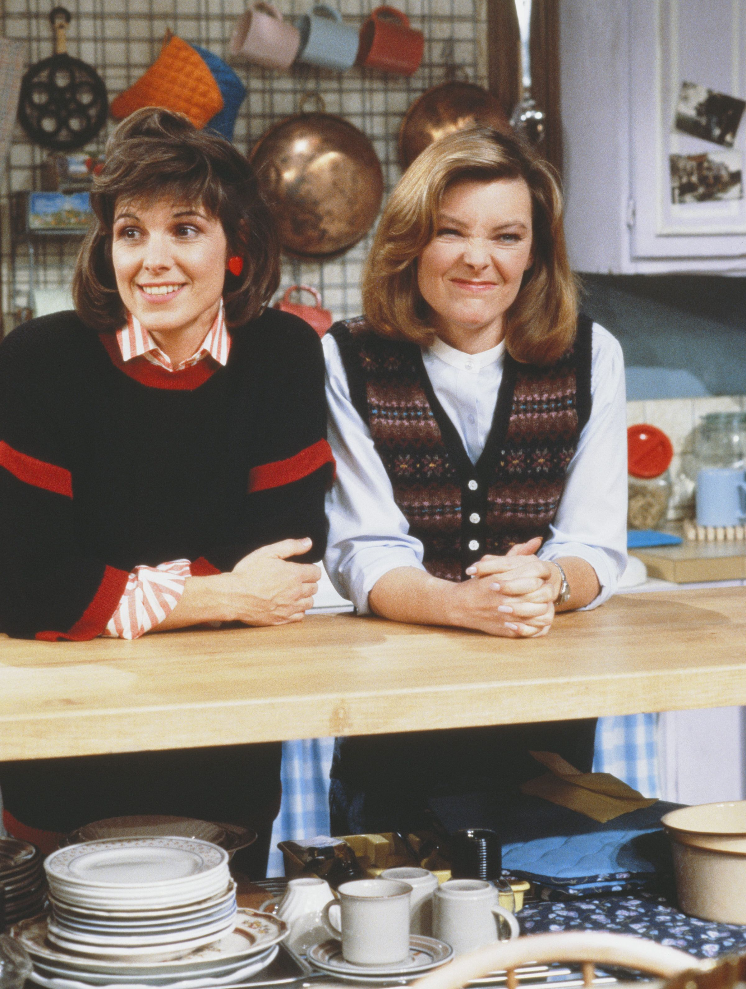 American actresses Susan Saint James (left) (as Kate McArdle) and Jane Curtin (as Allie Lowell) lean against a kitchen counter in a still from the CBS television sitcom 'Kate & Allie,' New York, New York, 1985. (Photo by CBS Photo Archive/Getty Images)