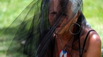 Aida Cruz Alicea, 68, prays while wearing a black veil in front of hundreds of shoes that were displayed in memory of those killed by Hurricane Maria in front of the Puerto Rican Capitol, in San Juan on June 1, 2018. - Hurricane Maria, which pummeled Puerto Rico in September 2017, is likely responsible for the deaths of more than 4,600 people, some 70 times more than official estimates, US researchers said Tuesday. (Photo by Ricardo ARDUENGO / AFP)        (Photo credit should read RICARDO ARDUENGO/AFP/Getty Images)