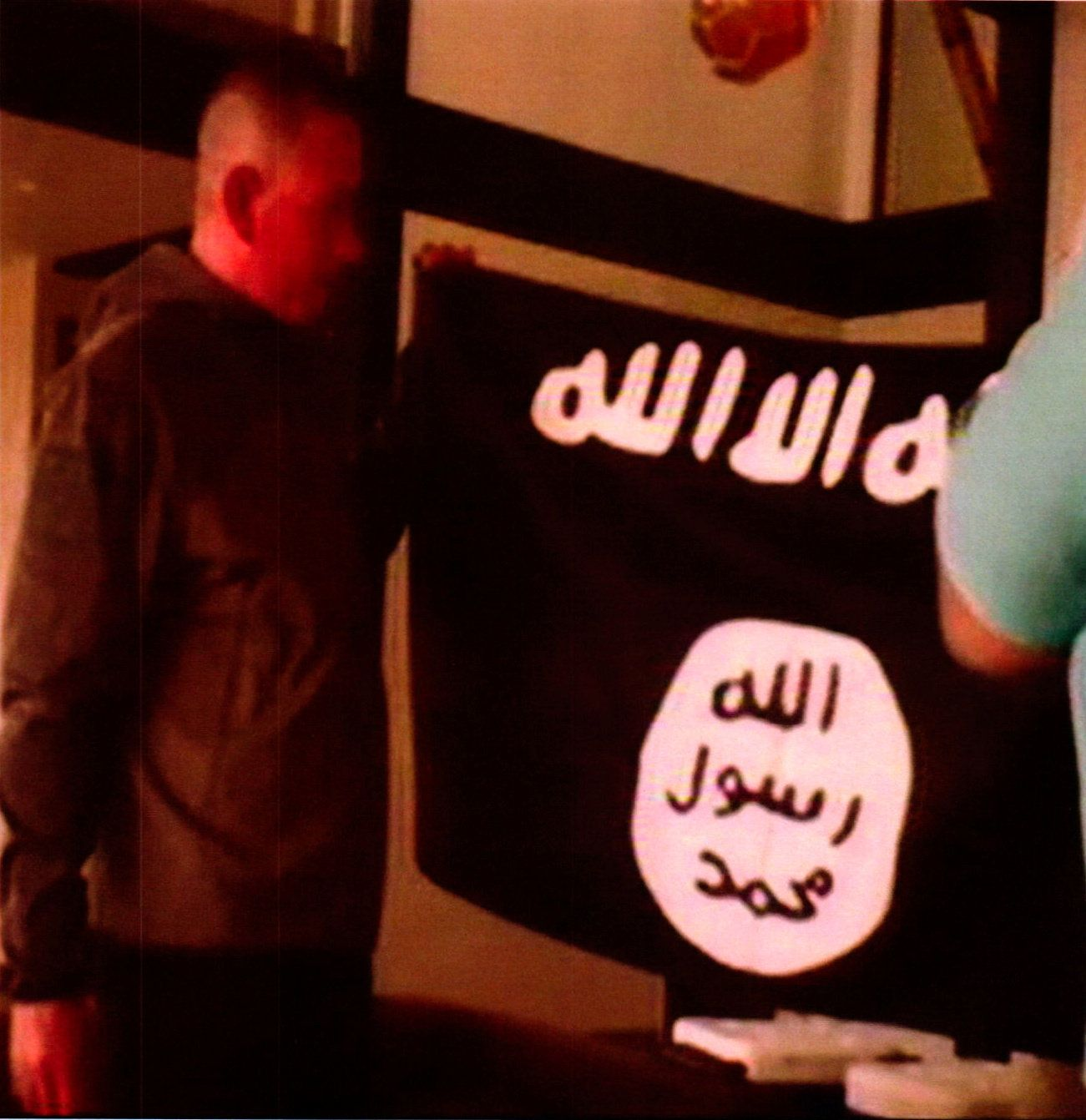 A photograph with a redacted date, and entered into federal court as an exhibit to support the government's motion to keep U.S. Army Sergeant Ikaika Erik Kang in detention without bond, shows what is described as Kang holding the Islamic State Flag after pledging allegiance to the Islamic State.  Kang is charged with trying to provide material support to Islamic State extremists. the U.S. District Court for the District of Hawaii/Handout via REUTERS   ATTENTION EDITORS - THIS IMAGE WAS PROVIDED BY A THIRD PARTY