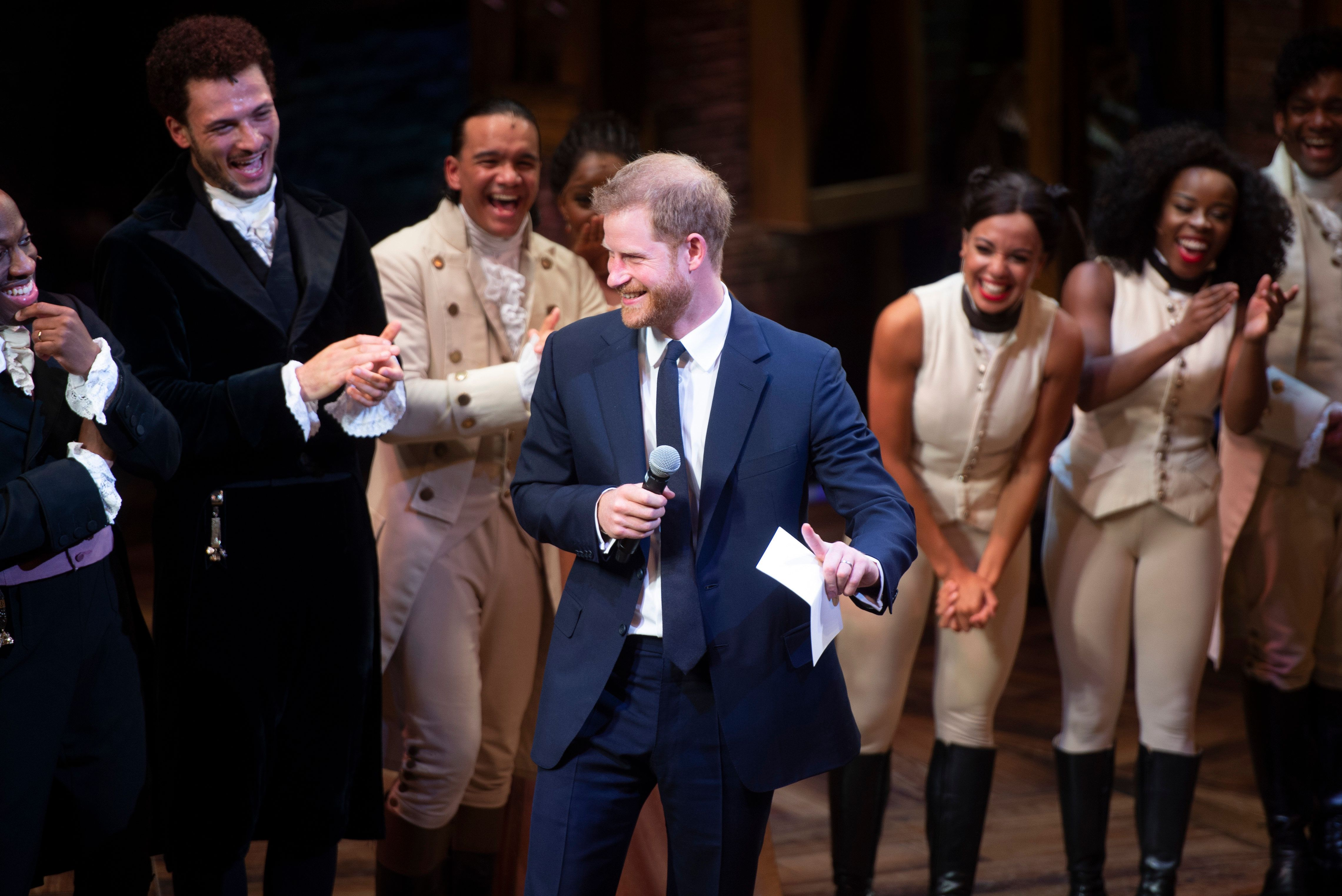 Britain's Prince Harry, Duke of Sussex (C) gives a speech with the cast and crew after a gala performance of the musical 'Hamilton' in support of the charity Sentebale at the Victoria Palace Theatre in London on August 29, 2018. (Photo by Dan Charity / POOL / AFP)        (Photo credit should read DAN CHARITY/AFP/Getty Images)