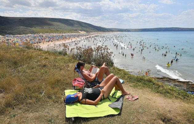 People sunbathe on the clifftop at Woolacombe Beach in North