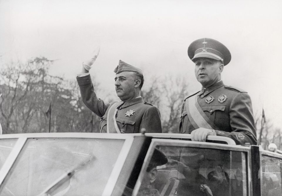 Franco (left) waves to the crowd as rides in a car with Minister of the Army Jose Varela during a parade...