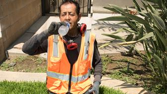 Fontana, California - July 29, 2018: Raudel Felix Garcia's brother Abdon Felix died in 2008 years ago from heat-related complications while working in the fields in California's Central Valley. About six years ago, Raudel started doing landscaping work, and thinks about how the heat affects him and his crew on a daily basis now. He wears long sleeves to protect himself from the sun, a hat to provide shade, and drinks plenty of water (sometimes upwards of 15-20 16 oz. bottles a day), and takes frequent breaks if needed when the temperatures are soaring over 100 degrees. (Melissa Lyttle for HuffPost)