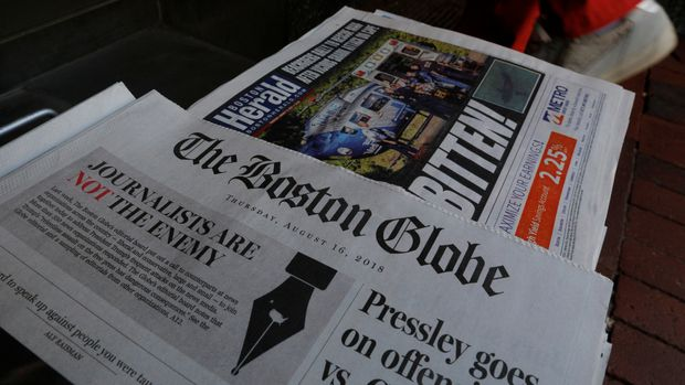 A customer walks past the front page of the Boston Globe newspaper referencing their editorial defense of press freedom and a rebuke of President Donald Trump for denouncing some media organizations as enemies of the American people, part of a nationwide editorial effort coordinated by the Boston Globe, at a newsstand in Cambridge, Massachusetts, U.S., August 16, 2018.     REUTERS/Brian Snyder