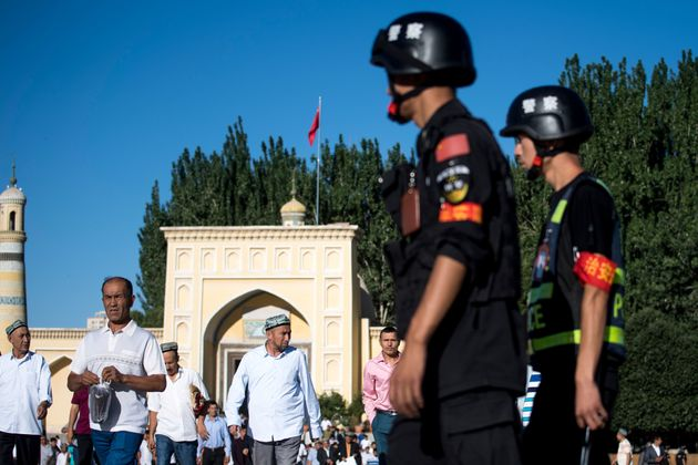 Police patrol as Muslims leave the Id Kah Mosque in June 2017 in the old town of Kashgar in China's Xinjiang...