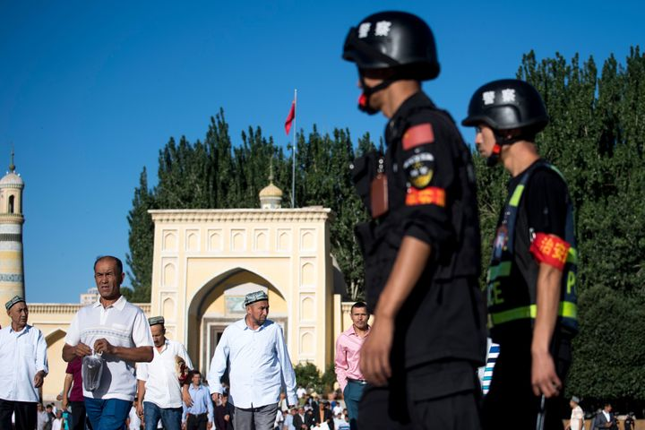 Police patrol as Muslims leave the Id Kah Mosque in June 2017 in the old town of Kashgar in China's Xinjiang Uighur Autonomou