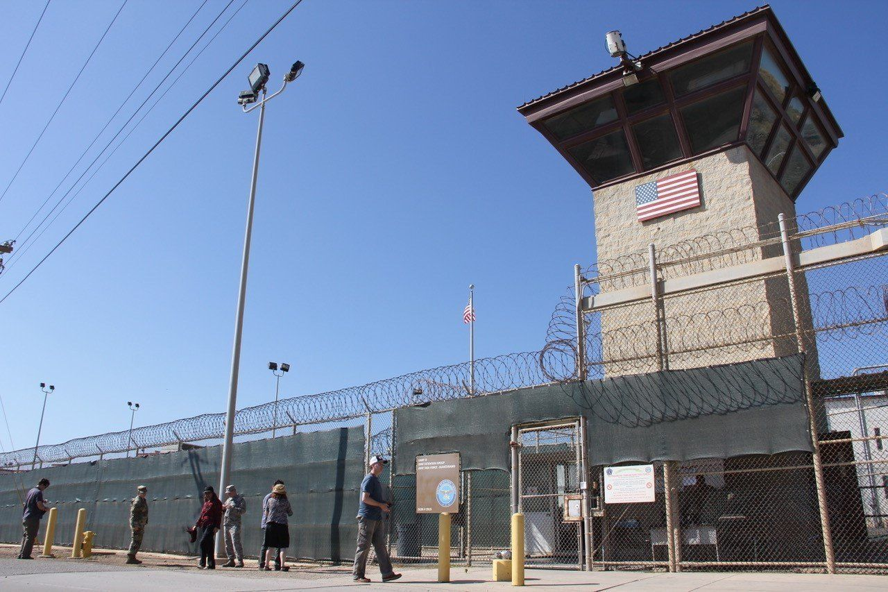 Poeple walk past a guard tower outside the fencing of Camp 5 at the US Military's Prison in Guantanamo Bay, Cuba on January 26, 2017. President Donald Trump has said he 'absolutely' thinks torture works, but doctors, lawyers for terror suspects, and even fellow Republicans have pledged to oppose any effort to reinstate waterboarding or other banned interrogation techniques. / AFP / Thomas WATKINS        (Photo credit should read THOMAS WATKINS/AFP/Getty Images)