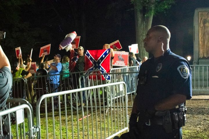 "A police officer stands behind the barricades as ""Silent Sam"" supporters raise Confederate flags and posters that say, ""Save"