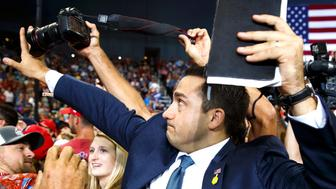 A volunteer member of the advance team for President Donald Trump blocks a camera as a photojournalist attempts to take a photo of a protester during a campaign rally at the Ford Center Thursday Aug 30 2018 in Evansville Ind