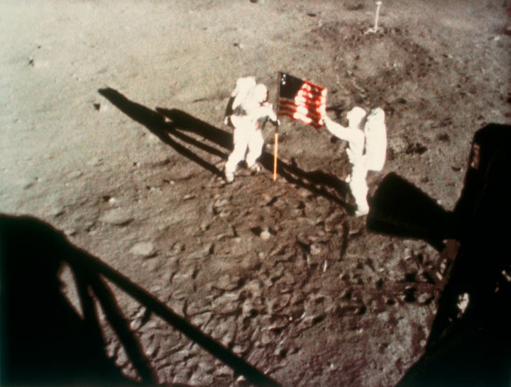 "Astronauts Neil Armstrong and Edwin ""Buzz"" Aldrin plant the American flag on Earth's moon on July 20, 1969."