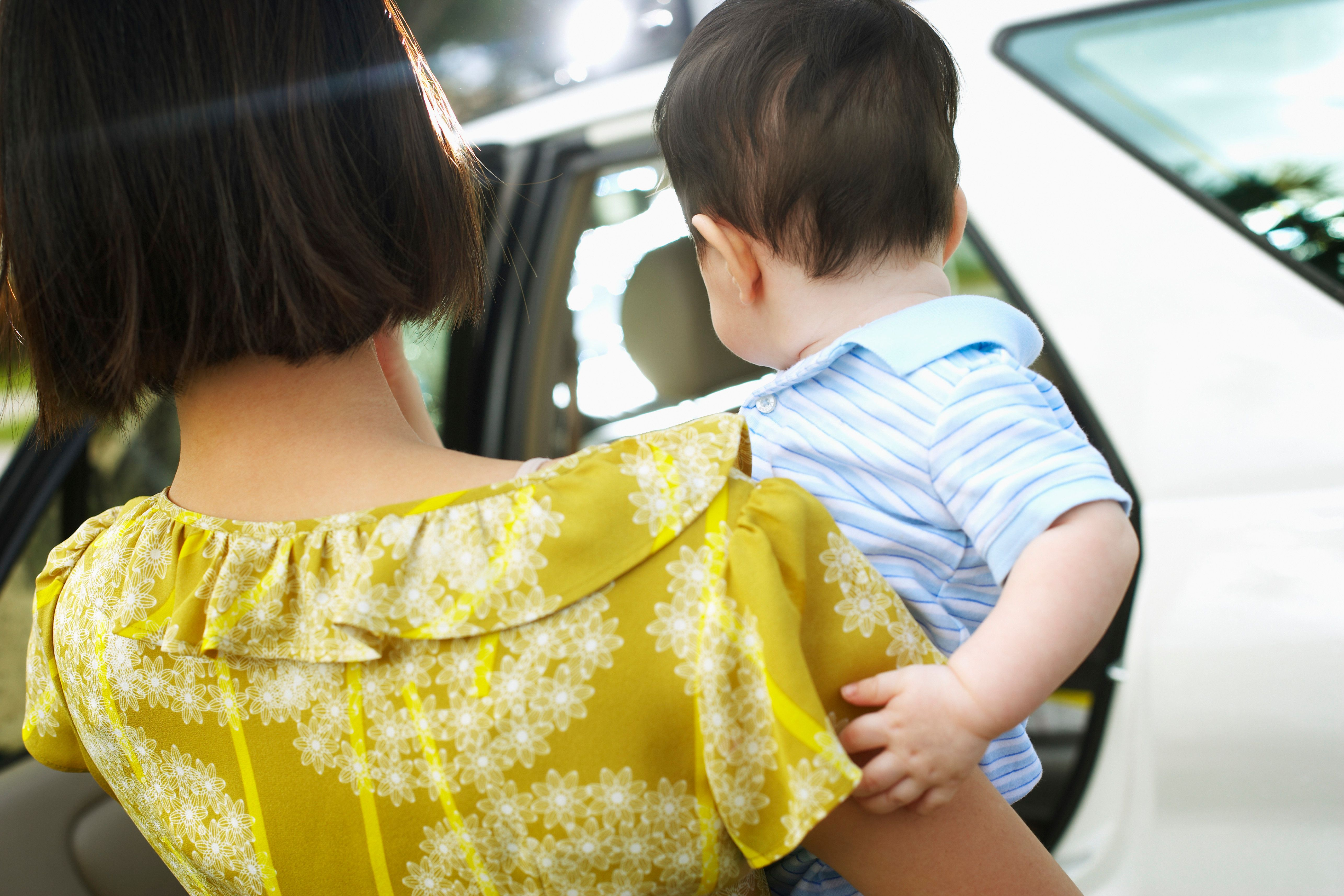 Mother Putting Baby in Car --- Image by � Randy Faris/Corbis