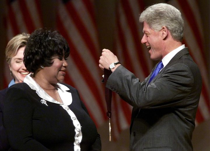 President Bill Clinton awards singer Aretha Franklin with a National Medal of the Arts in 1999 as first lady Hillary Clinton