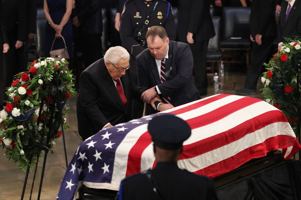 Former U.S. Secretary of State Henry Kissinger (left) honors the late senator.
