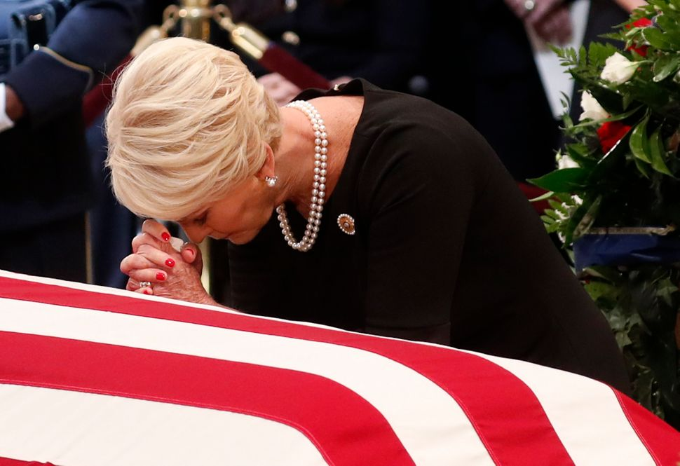 Cindy McCain, wife of the senator, prays at the casket of her husband.