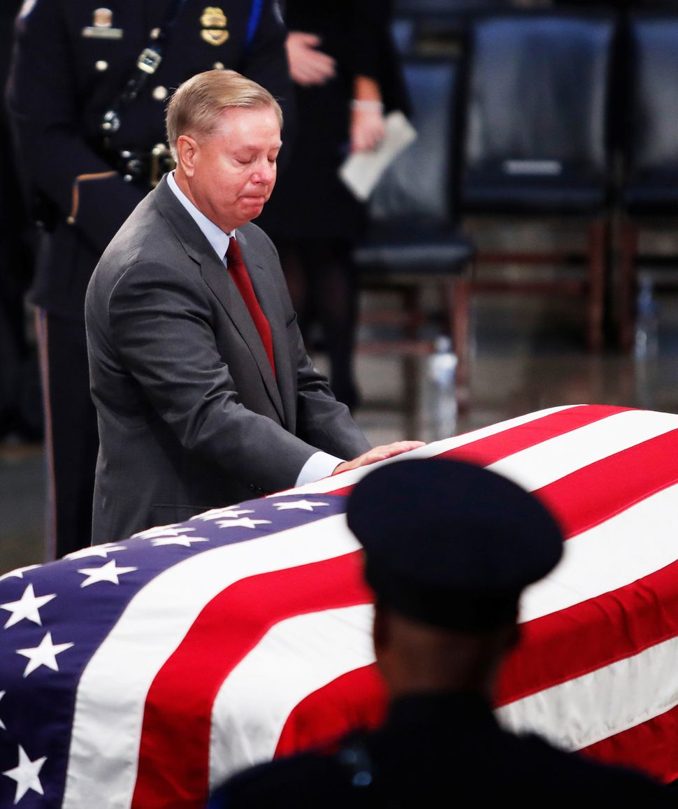 Sen. Lindsey Graham lays his hand on the casket.