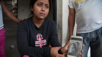 Elsa Johana Ortiz, 25, shows a picture of her with her 8-year-old son Antony Daniel Tobar Ortiz, during an interview about how U.S. immigration authorities separated them in Texas and deported her to her home country, as she gives an interview at her home in Palencia, Guatemala, Saturday, June 23, 2018. Ortiz said she's been separated from her son since May 27. (AP Photo/Luis Soto)