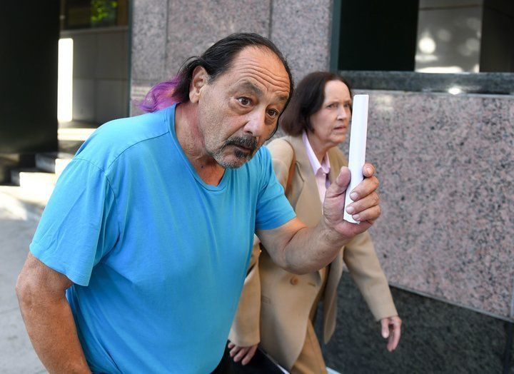 Suspect Robert Chain is leaving the Los Angeles courthouse after being released on bail on August 30, 2018. His wife, attorney Betsy Staszek Chain, is by his side. - A California man has been arrested for making death threats against employees of the Boston Globe, which recently organized a newspaper editorial response to attacks on the media by President Donald Trump. Robert Chain, 68, of Encino, California, was arrested on Thursday and charged with one count of making threatening communications, the US Attorney's Office for the District of Massachusetts said. Chain was to appear in federal court in Los Angeles later Thursday and would eventually be transferred to Boston, it said in a statement. (Photo by Mark RALSTON / AFP)        (Photo credit should read MARK RALSTON/AFP/Getty Images)