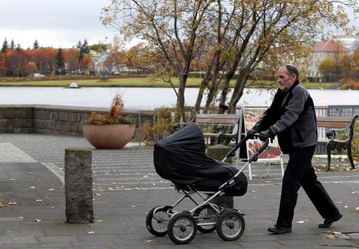 A man pushes a baby pram in a park in Reykjavik.