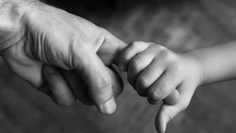 top view closeup of child holding his father index finger