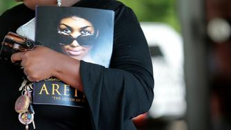A woman holds a program from Aretha Franklin's funeral at the Greater Grace Temple in on August 31, 2018 in Detroit, Michigan. (Photo by JEFF KOWALSKY / AFP)        (Photo credit should read JEFF KOWALSKY/AFP/Getty Images)