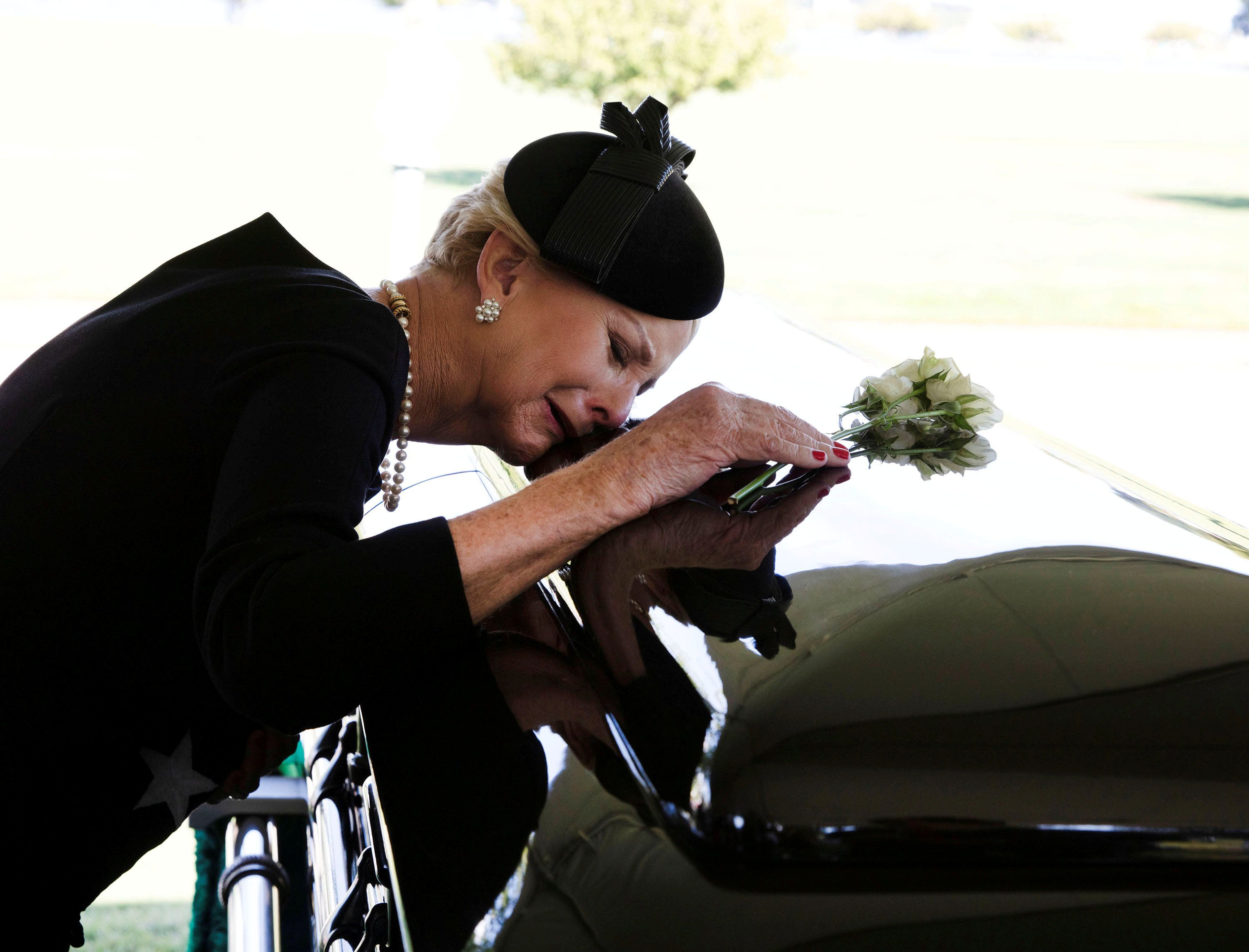 Cindy McCain lays her head on the casket of Sen. John McCain during a burial service at the cemetery at the United States Nav