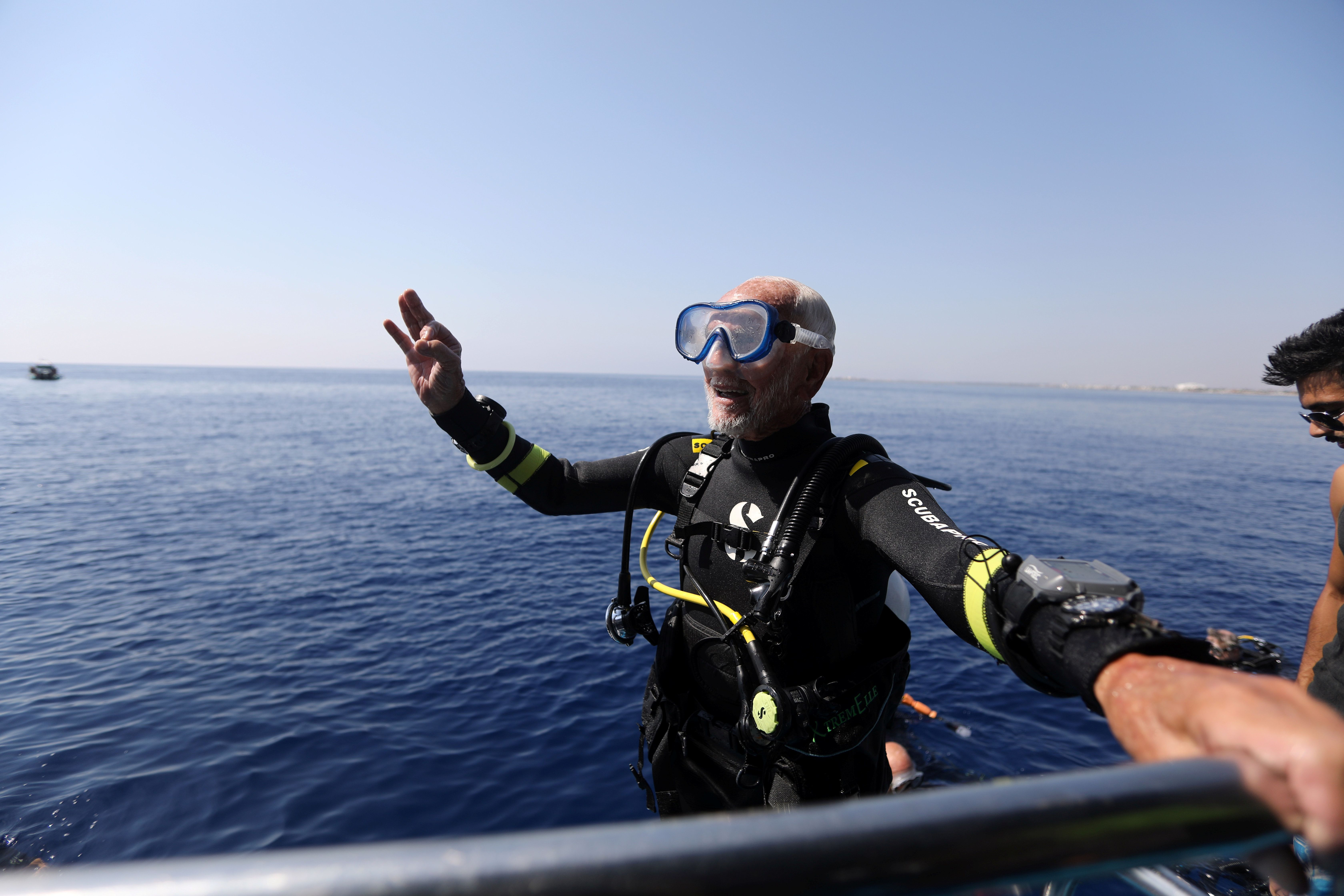 Ray Woolley, pioneer diver and World War 2 veteran, gestures after breaking a new diving record as he turns 95 by taking the plunge at the Zenobia, a cargo ship wreck off the Cypriot town of Larnaca, Cyprus September 1, 2018. REUTERS/Yiannis Kourtoglou