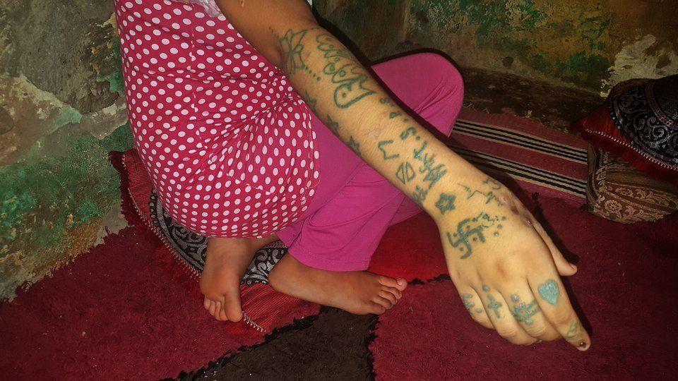 문신이 새겨진 팔을 보여주는 카디자의