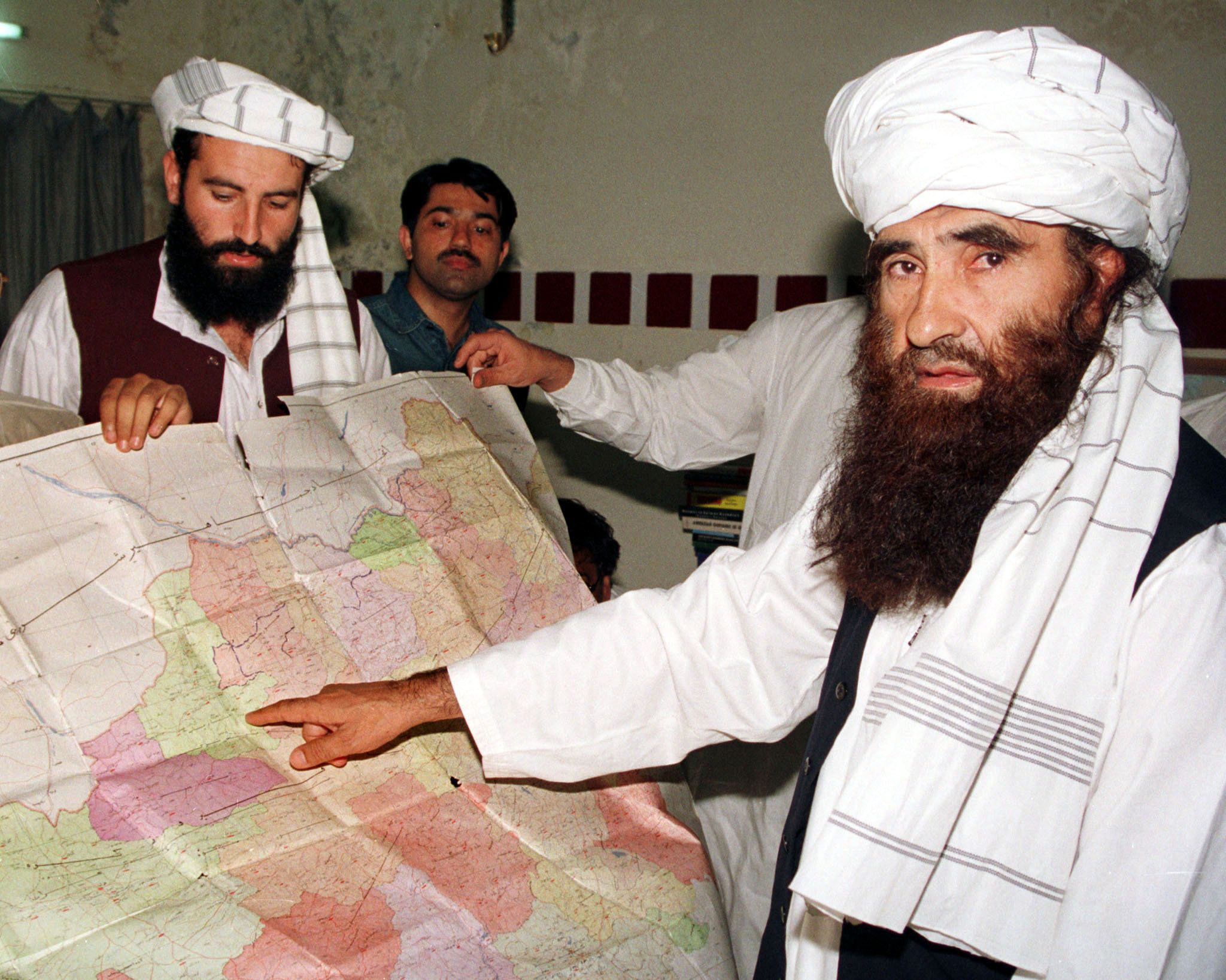 Jalaluddin Haqqani (R), the Taliban's Minister for Tribal Affairs, points to a map of Afghanistan during a visit to Islamabad, Pakistan while his son Naziruddin (L) looks on in this October 19, 2001 file photograph. Al Qaeda, the Pakistani Taliban and the Haqqani network -- blamed for a Sept. 13, 2011 attack on the U.S. embassy in Kabul --  picked the most ruthless fighters from their ranks in 2009 to form the Khurasan unit, for a special mission.  CIA pilots, who remotely operate the drones, could step up their pursuit of the Haqqani network leaders after an attack on the U.S. mission in Kabul last month.  To match feature PAKISTAN MILITANTS/HITSQUAD   REUTERS/Stringer/Files  (PAKISTAN - Tags: POLITICS CONFLICT)