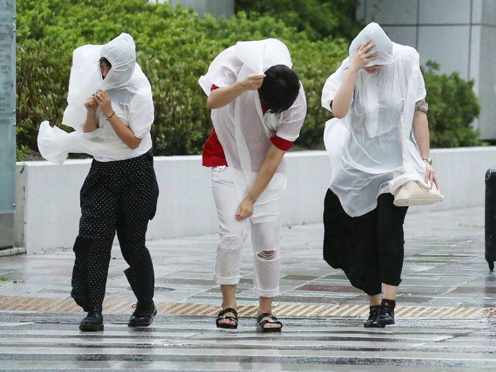People walk against strong winds in Nagoya, Japan.