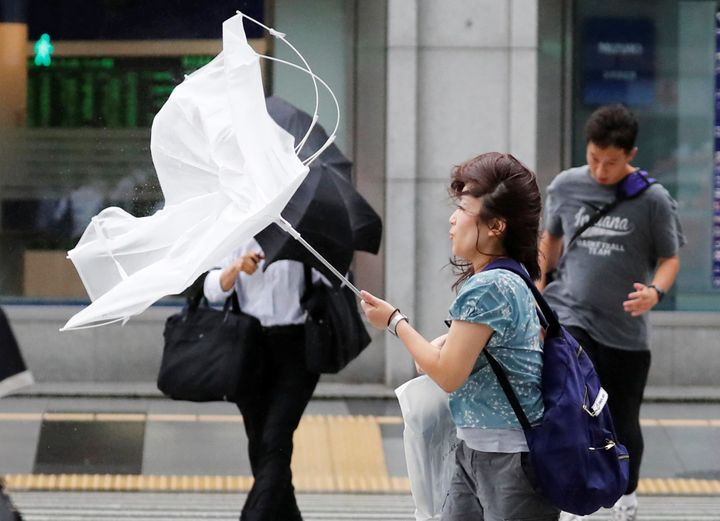 A woman using an umbrella struggles against strong wind and rain caused by Typhoon Jebi, in Tokyo.