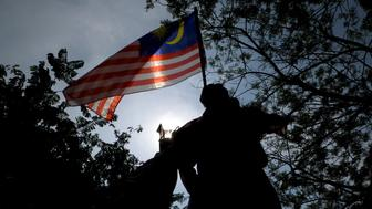Attendees are silhouetted as they hold a Malaysian flag during National Day celebrations in Putrajaya, Malaysia, on Friday, Aug. 31, 2018. Malaysian Prime MinisterMahathirMohamad this week said foreigners won't be allowed to buy property atCountry Garden Holdings Co.'s $100 billion project, or be granted visas to live there, adding to housing curbs around the world fueled by soaring home prices and populist politics. Photographer: Samsul Said/Bloomberg via Getty Images