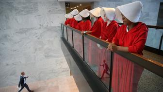 WASHINGTON, DC - SEPTEMBER 04:  Protesters dressed in The Handmaid's Tale costume, protest outside the hearing room where Supreme Court nominee Judge Brett Kavanaugh will testify before the Senate Judiciary Committee during his Supreme Court confirmation hearing in the Hart Senate Office Building on Capitol Hill September 4, 2018 in Washington, DC. Kavanaugh was nominated by President Donald Trump to fill the vacancy on the court left by retiring Associate Justice Anthony Kennedy. (Photo by Win McNamee/Getty Images)