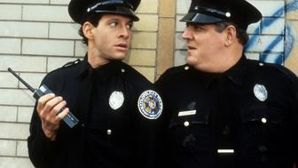 Steve Guttenberg looks to another cop in a scene from the film 'Police Academy 2: Their First Assignment', 1985. (Photo by Warner Brothers/Getty Images)