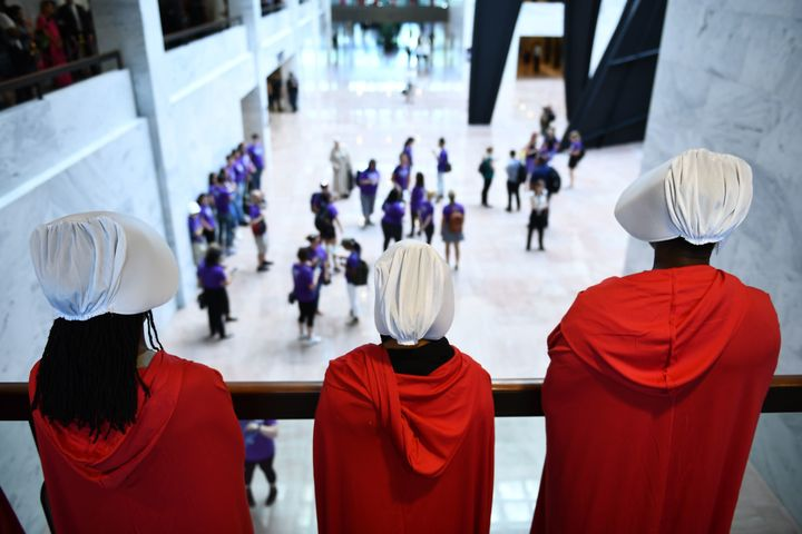 Women dressed as handmaids stood to protest Brett Kavanaugh.
