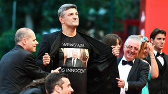 A man flashes a jersey reading 'Weinstein is innocent' as guests arrive for the premiere of the film 'Suspiria' presented in competition on September 1, 2018 during the 75th Venice Film Festival at Venice Lido. (Photo by Vincenzo PINTO / AFP)        (Photo credit should read VINCENZO PINTO/AFP/Getty Images)