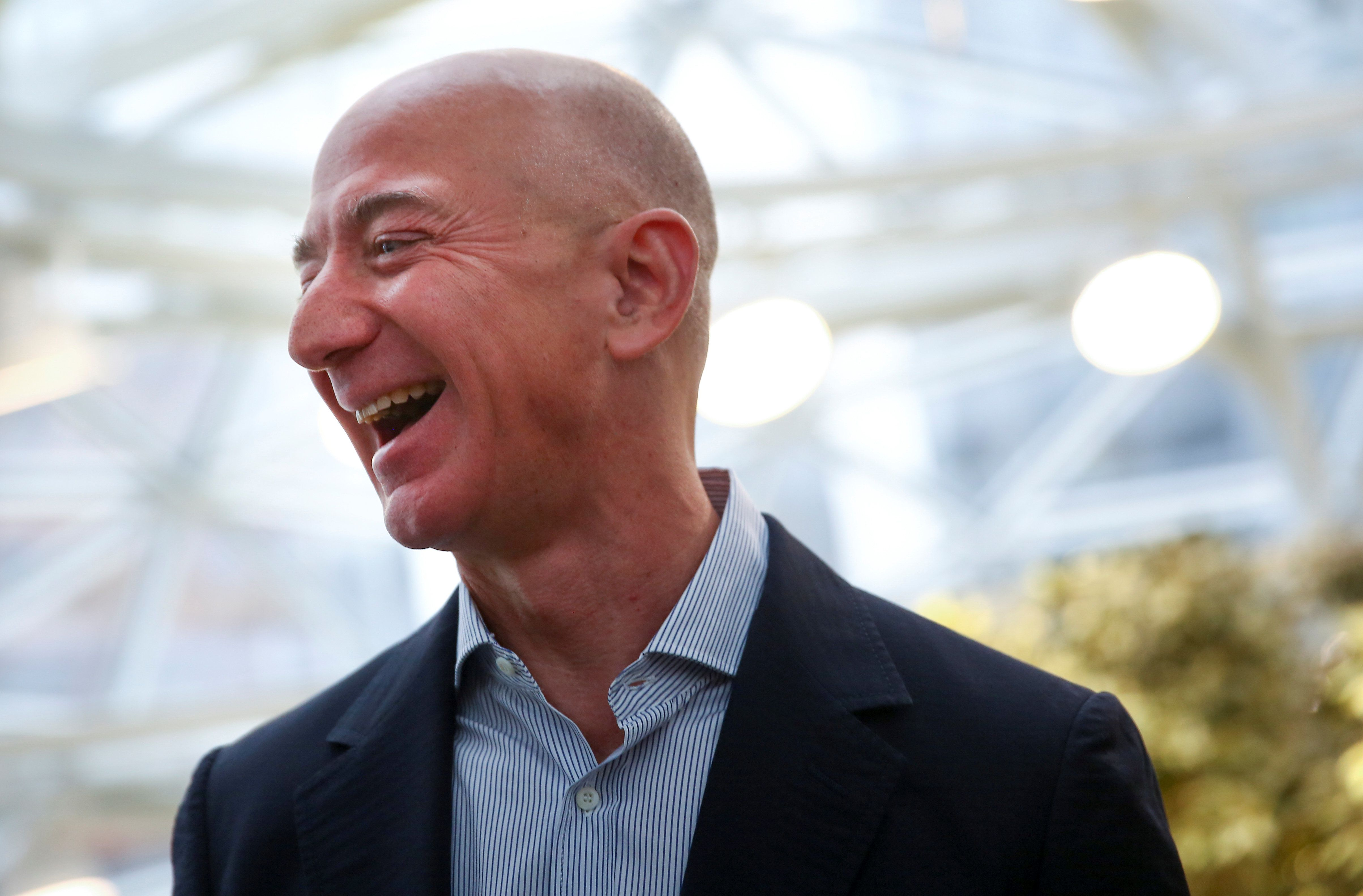 Amazon founder and CEO Jeff Bezos laughs as he talks to the media while touring the new Amazon Spheres during the grand opening at Amazon's Seattle headquarters in Seattle, Washington, U.S., January 29, 2018.   REUTERS/Lindsey Wasson