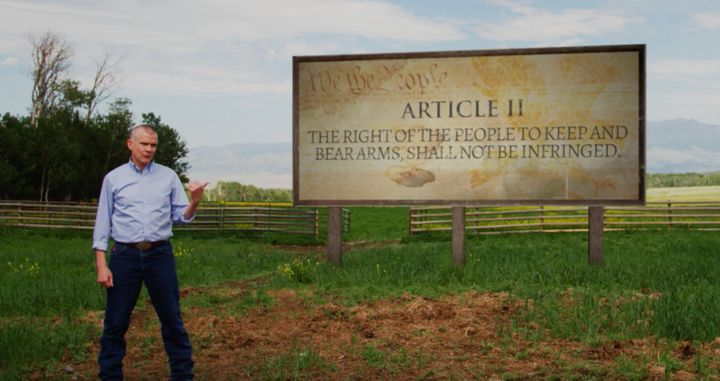 "Matt Rosendale poses with a sign that says ""Article II"" while referencing the Second Amendment."