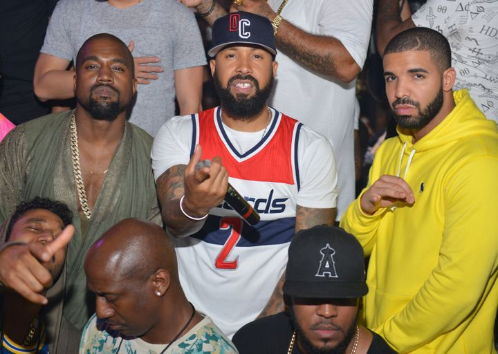 Kanye West and Drake pose together in 2015, albeit separated by industry executive Kenny Burns.